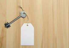 Étiquette de livre blanc attachée à la clé d'argent en métal sur le b en bois Photographie stock libre de droits