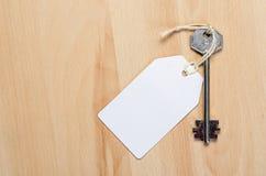 Étiquette de livre blanc attachée à la clé d'argent en métal sur le b en bois Photo stock