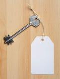 Étiquette de livre blanc attachée à la clé d'argent en métal sur le b en bois Images stock