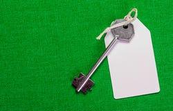 Étiquette de livre blanc attachée à la clé d'argent en métal sur le b vert Image stock