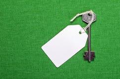 Étiquette de livre blanc attachée à la clé d'argent en métal sur le b vert Photographie stock