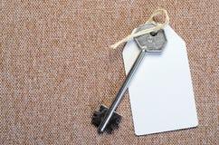 Étiquette de livre blanc attachée à la clé d'argent en métal sur le Ba brun Photographie stock