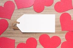Étiquette de papier avec la frontière de papier en forme de coeur rouge de jour de valentines sur le fond en bois Image libre de droits