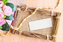 Étiquette de papier blanc dans le cadre de photo de sac avec la belle fleur Photos libres de droits