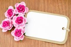 Étiquette de papier blanc et roses roses Images stock