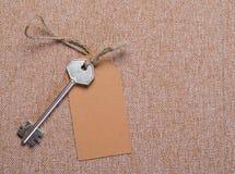 Étiquette de papier de Brown attachée à la clé d'argent en métal sur le Ba Photo libre de droits
