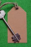 Étiquette de papier de Brown attachée à la clé d'argent en métal sur le f vert Photo stock
