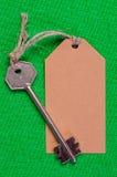 Étiquette de papier de Brown attachée à la clé d'argent en métal sur le f vert Photo libre de droits