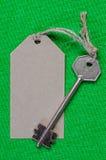 Étiquette de papier grise attachée à la clé d'argent en métal sur le f vert Photos libres de droits