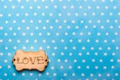 Étiquette en bois avec amour de mot sur le bleu Images libres de droits