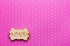 Étiquette en bois avec amour de mot sur le rose Image libre de droits