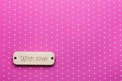 Étiquette en bois avec amour de mot sur le rose Image stock