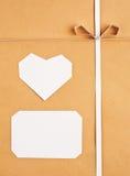 Étiquette et coeur de papier fabriqué à la main sur le papier d'emballage comme fond. Image libre de droits