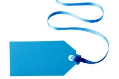 Étiquette ou label bleue de cadeau avec le long ruban bouclé d'isolement sur le backg blanc Images stock