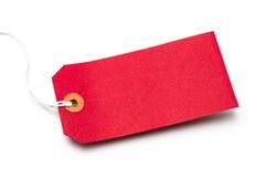Étiquette rouge de bagage de carton ou de papier d'isolement sur le blanc Photographie stock