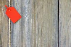 Étiquette rouge vide sur le fond en bois Image libre de droits