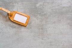 Étiquette vide de valise faite de cuir brun sur le fond concret image stock