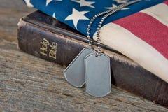 Étiquettes de chien militaires sur la bible Images stock