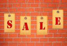 Étiquettes de vente au-dessus de mur de briques Photos stock