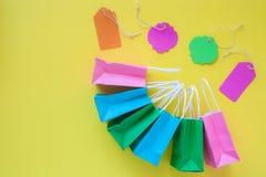 Étiquettes de vente et sacs en papier colorés d'achats sur le dos lumineux de jaune Photographie stock libre de droits