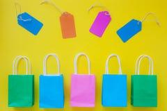 Étiquettes de vente et sacs en papier colorés d'achats sur le dos lumineux de jaune Photographie stock