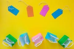 Étiquettes de vente et sacs en papier colorés d'achats sur le dos lumineux de jaune Image libre de droits