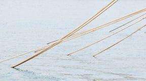 Étiré amarrant des cordes sortant de l'eau de mer image libre de droits