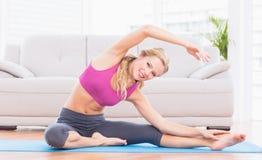 Étirage blond convenable sur le tapis d'exercice souriant à l'appareil-photo Images libres de droits
