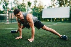 Étirage de l'exercice sur la séance d'entraînement extérieure de forme physique image libre de droits