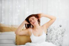 Étirage de la femme dans le lit pendant le matin Photos stock