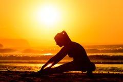 Étirage des exercices sur la plage au coucher du soleil Photo libre de droits