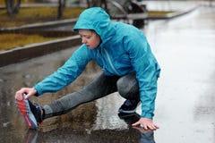 Étirage fonctionnant Femme de coureur étirant la jambe comme échauffement avant photo libre de droits