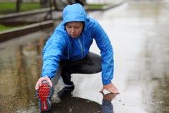 Étirage fonctionnant Plan rapproché des chaussures de course, femme étirant l image libre de droits