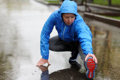Étirage fonctionnant Plan rapproché des chaussures de course, femme étirant l photographie stock libre de droits