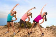 Étirant des femmes dehors sur la colline de hausse près de la portée de négligence de plage d'océan vers le ciel Photo libre de droits