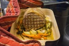 Étoffez commun préparent pour entrer dans le four Légumes dessous avec se tenir de gants de four photo stock
