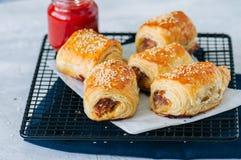 Étoffez et les petits pains de saucisse caramélisés d'oignon d'un plat en bois avec Image libre de droits