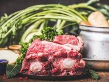 Étoffez la viande de queue de boeuf sur la table de cuisine avec faire cuire le pot et l'ingrédient de légumes, vue de côté Photographie stock libre de droits