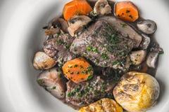 Étoffez le bourguignon dans un plat en céramique avec les pommes de terre grillées Image libre de droits