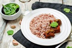 Étoffez le cuiseur lent avec du riz rouge et blanc et des verts Photo libre de droits