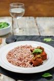 Étoffez le cuiseur lent avec du riz rouge et blanc et des verts Images stock