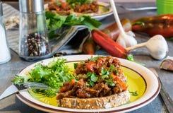 Étoffez le mélange de viande avec les tomates et le poivre sur le pain frit, herbacé Grand dîner Photographie stock libre de droits