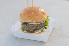 Étoffez le serverd de petit pain d'hamburger et de sauce et de sésame à mayonnaise sur la boîte de papier Photos stock