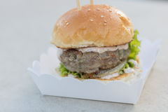 Étoffez le serverd de petit pain d'hamburger et de sauce et de sésame à mayonnaise sur la boîte de papier Photo libre de droits
