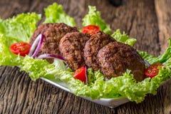 Étoffez les côtelettes de boulettes de viande d'hamburgers à l'oignon de tomate de salade de laitue sur le conseil en bois images libres de droits
