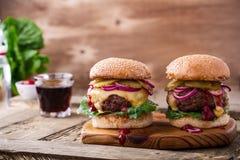 Étoffez les hamburgers avec les cornichons, l'oignon rouge et la laitue photos stock