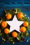 Étoile blanche rougeoyante de LED entourée avec les mandarines fraîches et les branches impeccables avec des lumières de guirland photos libres de droits