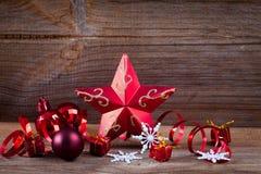 Étoile, cadeaux et bandes rouges sur le panneau en bois Photographie stock libre de droits