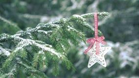 Étoile de décoration de Noël accrochant sur l'arbre de sapin neigeux banque de vidéos