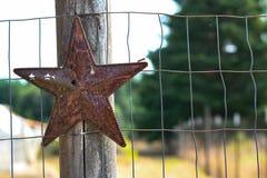 Étoile en métal sur le poteau en bois de barrière photographie stock
